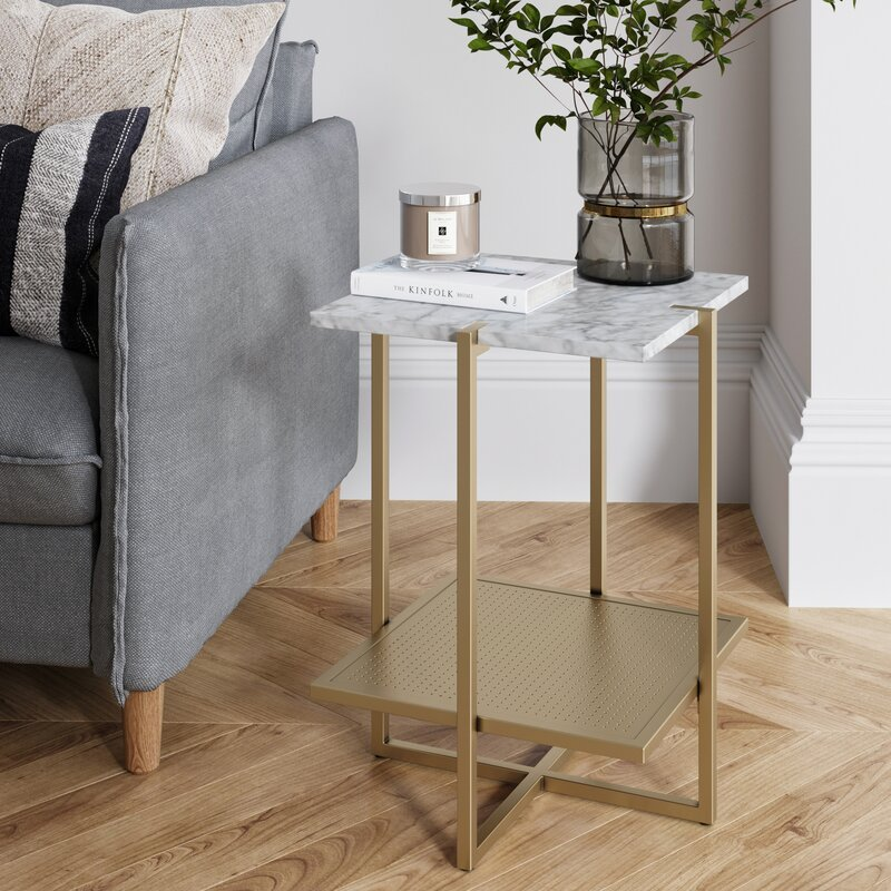 Wrought Studio Flaunt your decorative pieces on this elegant accent table. Marble laminate top and geometric frame base add a touch of style to this two-tier furniture.Features: End table can hold up to 50 lbs Modern contemporary design Has pre-applied protector pad to keep your floor scratch free Quality material and strong construction Free returns within 90 days Set: No Set Type: Number of Tables Included: Pieces Included: Top Shape: Square Top Color: Base Color: Top Material: Faux Marble Top Material Details: Marble Laminate MDF Board Top Wood Construction Details: Top Wood Species: Wood Tone: Base Material: Metal Base Material Details: Powder coated steel Base Wood Construction Details: Base Wood Species: Reclaimed Wood: Purposeful Distressing Type: No Distressing Natural Variation Type: No Natural Variation Gloss Finish: No Mirrored: No Glass Component: Base Type: Frame Adjustable Height: No Shelves Included: No Number of Shelves: Drawers Included: No Number of Drawers: Cabinets Included: No Trunk Storage: No Tray Top: No Foldable: No Magazine Rack: No Wheels Included: No Lighted: No Wattage per Bulb: Bulb Included: EU Energy Efficiency Class: Weight Capacity: 50 Country of Origin: China Made in USA: No Supplier Intended & Approved Use: Residential Use Application Type: Wrought Iron: No LSB Investment Skus: AllModern - Wave 1Spefications: Certifications: SCS Certified: GREENGUARD Certified: TÜV Rheinland zertifiziert: Stiftung Warentest Note: Blauer Engel: PEFC Certified: ISO 9001 Certified: ISO 14001 Certified: FIRA Certified: ITTO Compliant: ISO 9000 Certified: ISO 14000 Certified: GSA Approved: GreenSpec: CALGreen Compliant: ANSI/BIFMA X7.1 Standard for Formaldehyde & TVOC Emissions: ANSI/BIFMA M7.1 Standard Test Method for Determining VOC Emissions: Commercial OR Residential Certifications: UL Listed: EPP Compliant: FSC Certified: TAA Compliant: Fire Rated: CPG Compliant: CE Certified: ADA Compliant: Energy Star Compliant: SATRA Approved: FISP Certified: California Proposition 65 Warning Required: General Certificate of Conformity (GCC): Yes ISTA 3A or 6A Certified: ISTA 1A Certified: Composite Wood Product (CWP): No CARB Phase II Compliant (formaldehyde emissions): TSCA Title VI Compliant (formaldehyde emissions): CAL TB 117-2013 Compliant: No Qi Wireless Charging Product Certification: Dimensions: Overall Height - Top to Bottom: 22 Overall Width - Side to Side: 16 Overall Depth - Front to Back: 16 Overall Product Weight: 21 Table Top Thickness: 1 Clearance - Floor to Bottom: 5 Shelving: No Shelf Height - Top to Bottom: Drawer: No Drawer Interior Height - Top to Bottom: Drawer Interior Width - Side to Side: Drawer Interior Depth - Front to Back: Largest Table: No Large Table Height - Top to Bottom: Large Table Width - Side to Side: Large Table Depth - Front to Back: Middle Table: No Middle Table Height - Top to Bottom: Middle Table Width - Side to Side: Middle Table Depth - Front to Back: Smallest Table: No Small Table Height - top to Bottom: Small Table Width - Side to Side: Small Table Depth - Front to Back: Assembly: Easy 20-minute assembly Level of Assembly: Full Assembly Needed Assembly Required: Yes Suggested # of People: 1 Estimated Time to Assemble: 20 Estimated Time to Assemble [Internal]: Additional Tools Required: Screw Driver;Power Drill Avoid Power Tools: No # of Pieces to be Assembled: 5 # of Hardware Pieces Included: 17 # of Steps Required: 5Warranty: Product Warranty: 5 Years Commercial Warranty: No Color: White/Gold