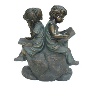Two Kids Reading On A Stone Statue