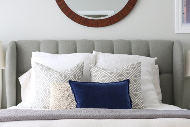 a grey linen headboard with a large round wooden mirror hung above