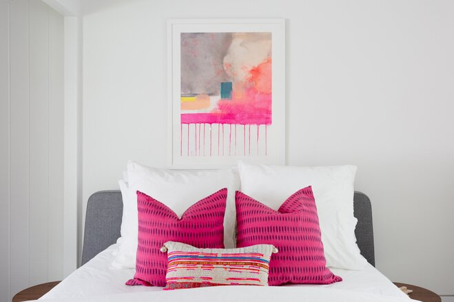 A Simple White Painted Bedroom With Linen Bedspread And Vibrant Pops Of Pink In Pillows