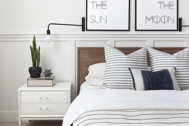 A Simple Modern White Bedroom With Gray Striped Sheets