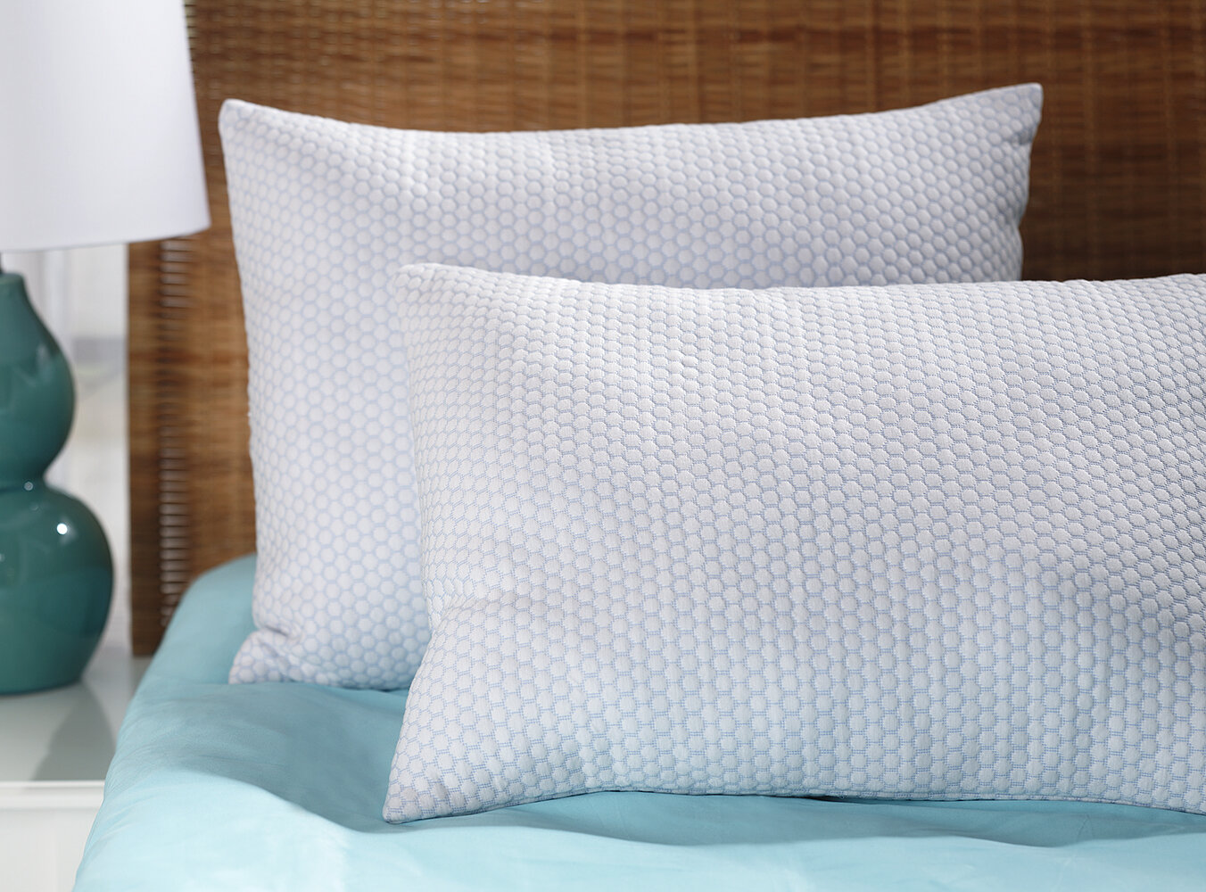 Two clean, white pillows on blue bedding