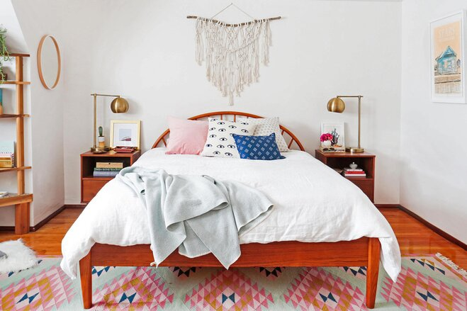 boho bedroom with a white linen duvet accent pillows in pink and blue a