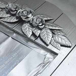 Flower and leaves detail on a silver mirror frame.