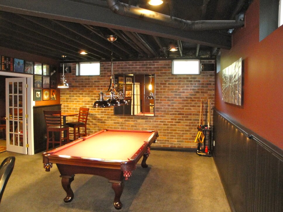 Pool area in room treated with molding and chair rail painted black and lit from beneath with drink shelf.  Real brick wall added to bring texture.  Large mirror on wall conceals utility access panel. Modern & Contemporary Rec Rooms Design
