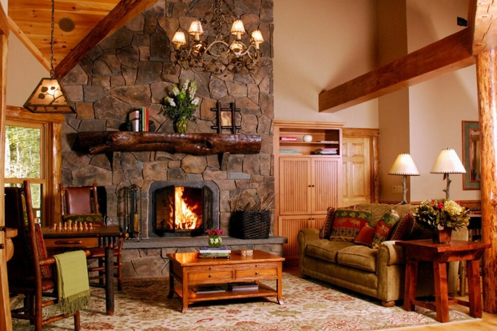 A rustic Andirondack style great room with a fieldstone fireplace facade, log posts, custom furnishings and lighting.   Photography byPicture This Studios Rustic Living Room Design