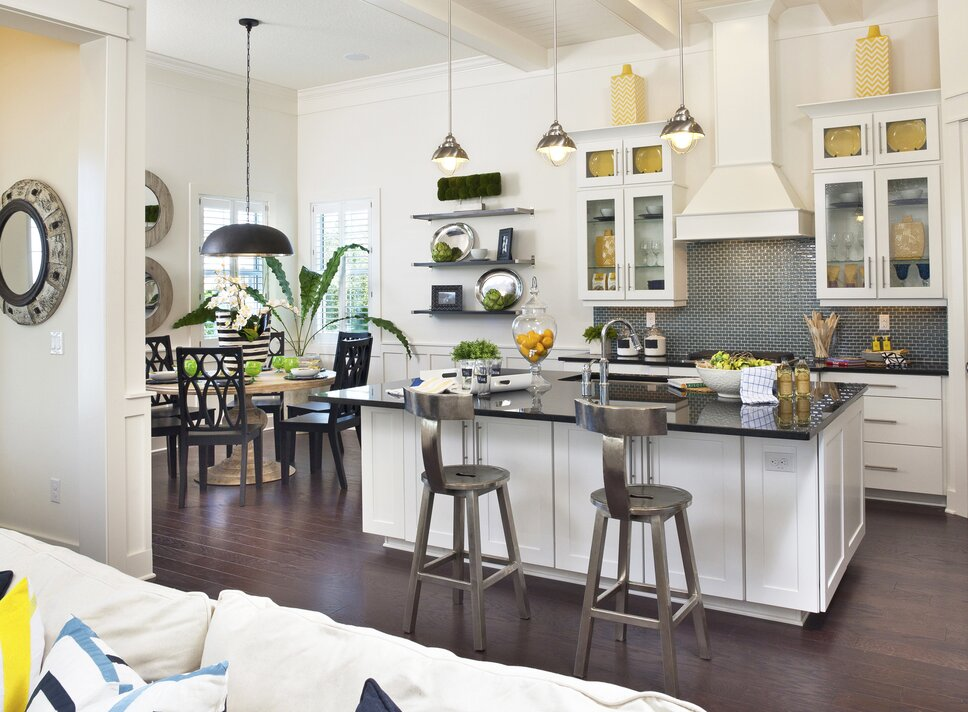 This award-winning kitchen design seamlessly blends a coastal-cottage feel with industrial-inspired elements. From the beadboard ceiling, to glass front white cabinets, this kitchen is the star of this beachside cottage. Eclectic Kitchen Design